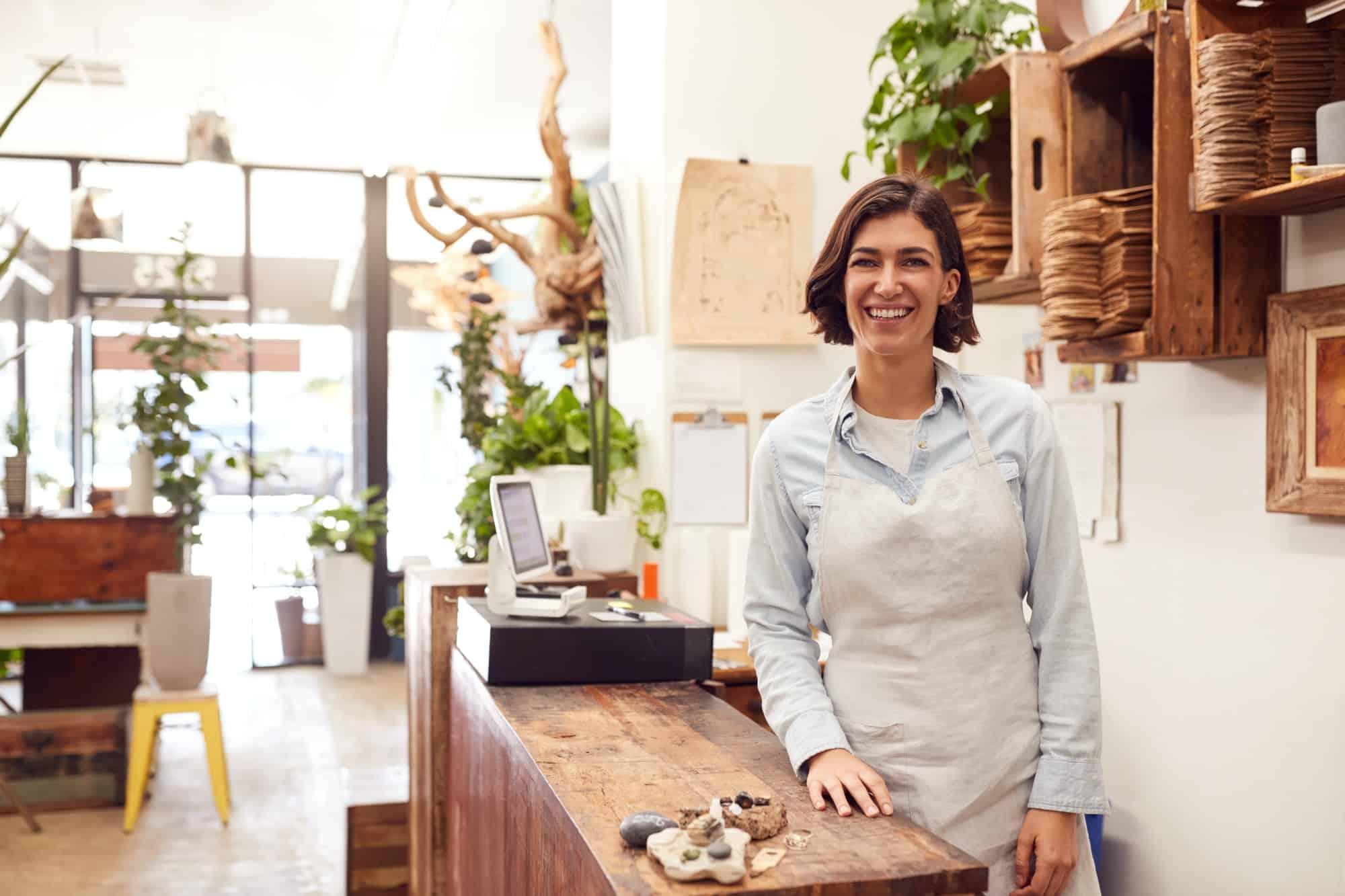 Portrait Of Smiling Female Sales Assistant Standing Behind Sales Desk Of Florists Store